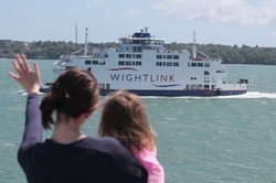 Woman and child waving at a Wightlink ferry