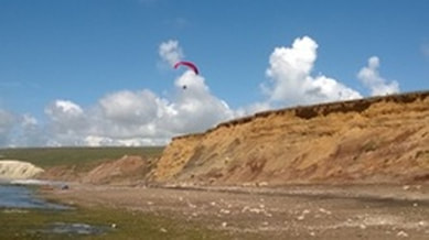 Paraglider over the cliffs at Compton Bay
